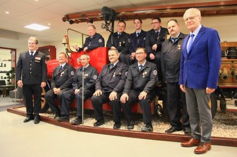 Gruppenbild der geehrten mit altem Feuerwehrfahrzeug mit Ralf Ackermann (links) und Herbert Hunkel (rechts)