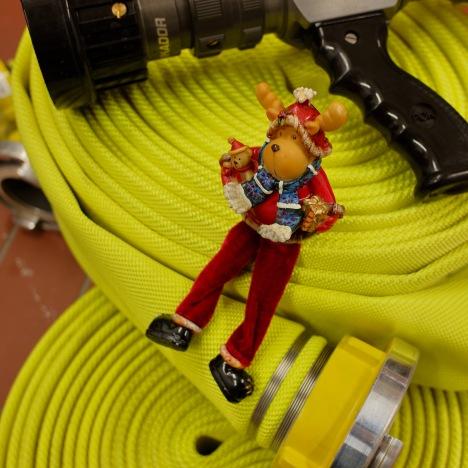 Schläuche der Feuerwehr mit Strahlrohr und mit einer Weihnachtsfigur